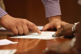 Hands pointing at an important document