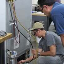 People working on a major appliance