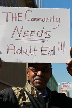 pic of a man holding a sign that state the community needs adult ed